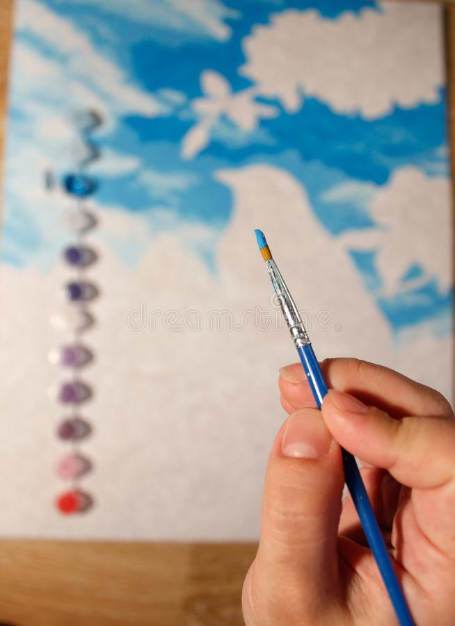 Hold a brush with acrylic paint in your hand. drawing a picture by numbers. set for creativity and needlework at home. vertical. Hold a brush with acrylic paint royalty free stock photo
