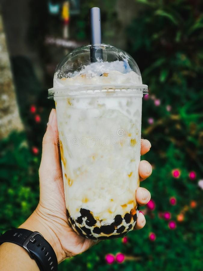 Hold Bubble milk tea in plastic cup on hand in Blurry green garden. Drink and relaxing in nature stock photos