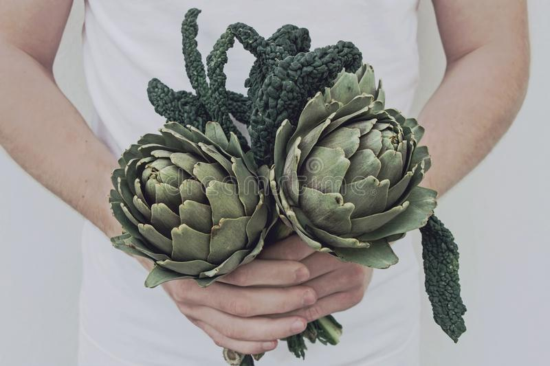 Hold fresh artichoke and kale in hand. Hold fresh artichoke and kale leaf in hand n stock photo
