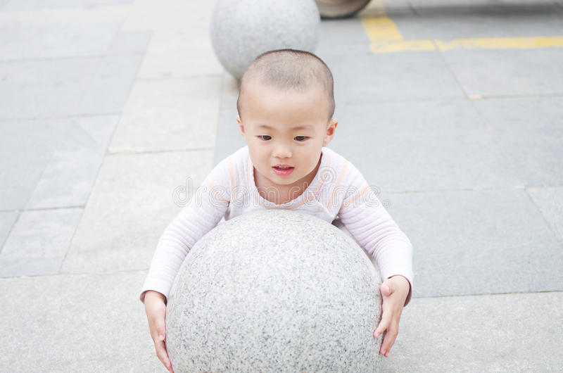 Hold up. A child trying to hold up the stone sphere royalty free stock images