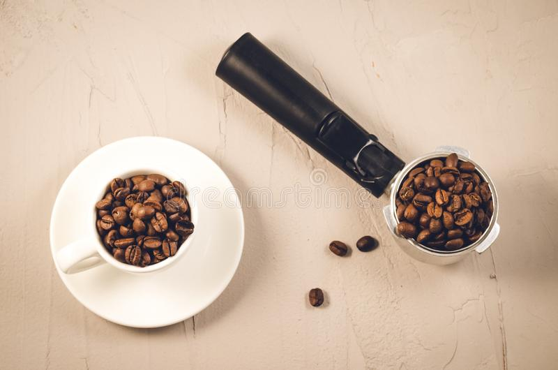 Holder for coffee maker, cup and scattered beans/holder for coffee maker, white cup and scattered beans. Top view stock photos