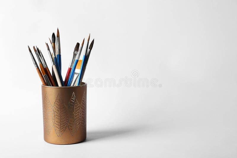 Holder with different paint brushes on white. Space for text. Holder with different paint brushes on white background. Space for text stock photography