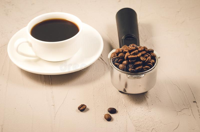 Holder filled with beans and coffee cup/holder filled with beans and coffee cup on a stone background, selective focus. Espresso maker white brown filter drink stock photo