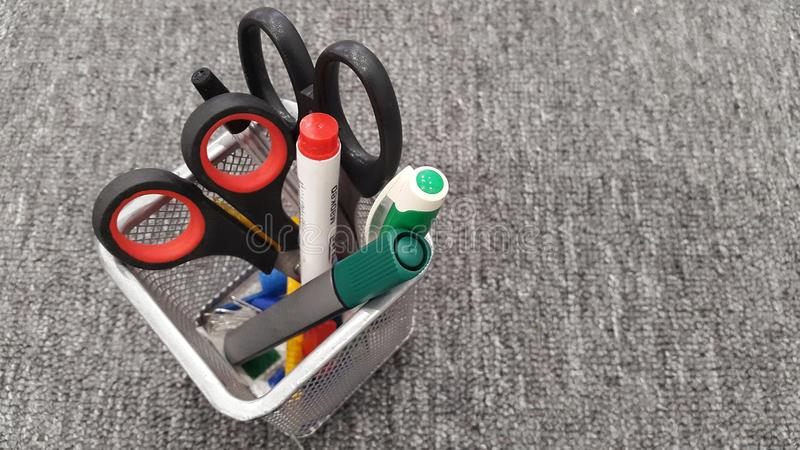 Pen and Pencil Holder on Desk. Close up of an assortment of pens, pencils, markers, and other writing instruments in a colorful pencil holder on an office desk royalty free stock photos