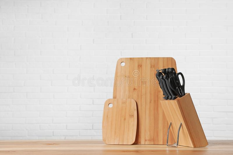 Holder with knives and clean boards on table against white brick wall. Space for text stock image