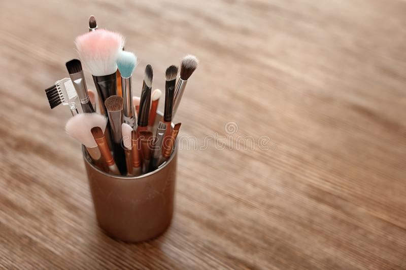 Holder with makeup brushes. On wooden table stock images