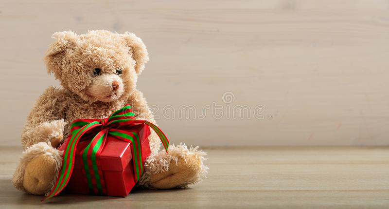 Holdimg d'ours de nounours un cadeau sur un plancher en bois images libres de droits
