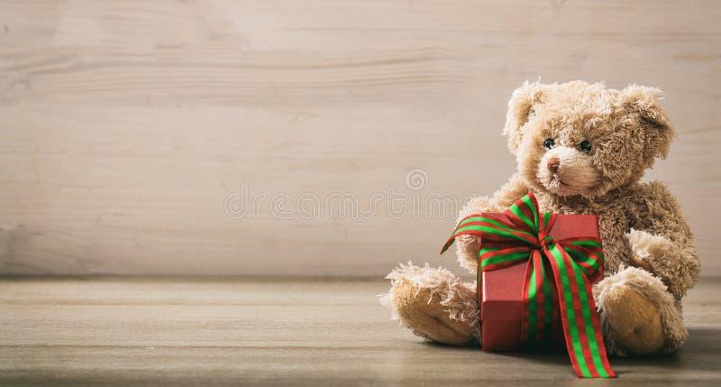 Holdimg do urso de peluche um presente em um assoalho de madeira fotos de stock royalty free