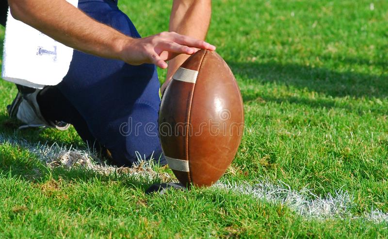 Holding The Ball For The Kick. The holders sets the ball up on the tee for the kickers to try the field goal or the extra point during the football game royalty free stock photos