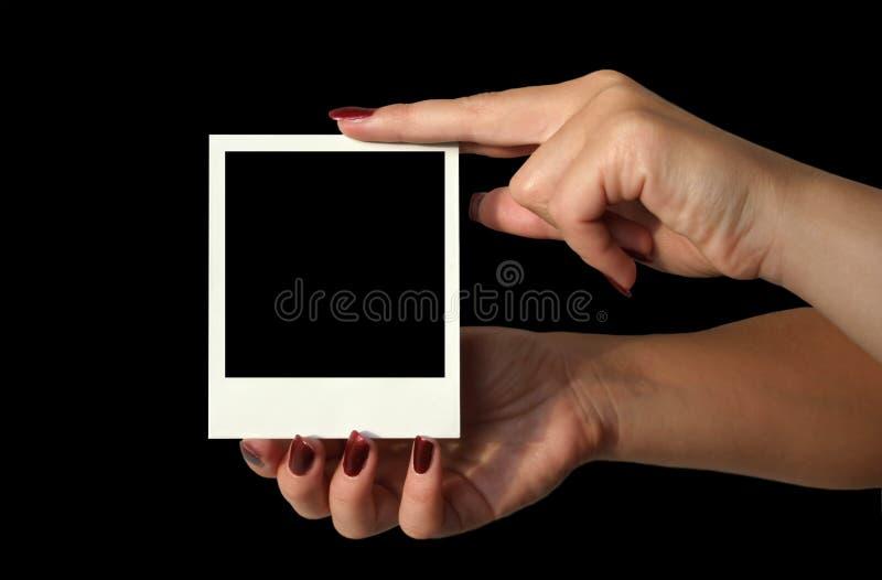 Holding blank polaroid - deep black background #2 royalty free stock image