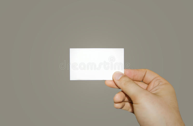 Holding a business card. A man holding a white business card royalty free stock images
