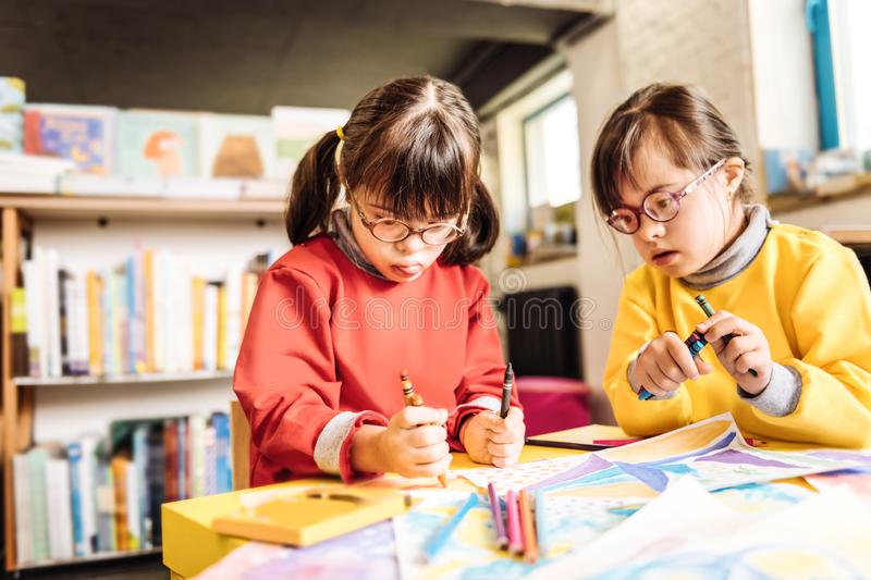 Funny sisters having Down syndrome holding crayons while drawing stock images