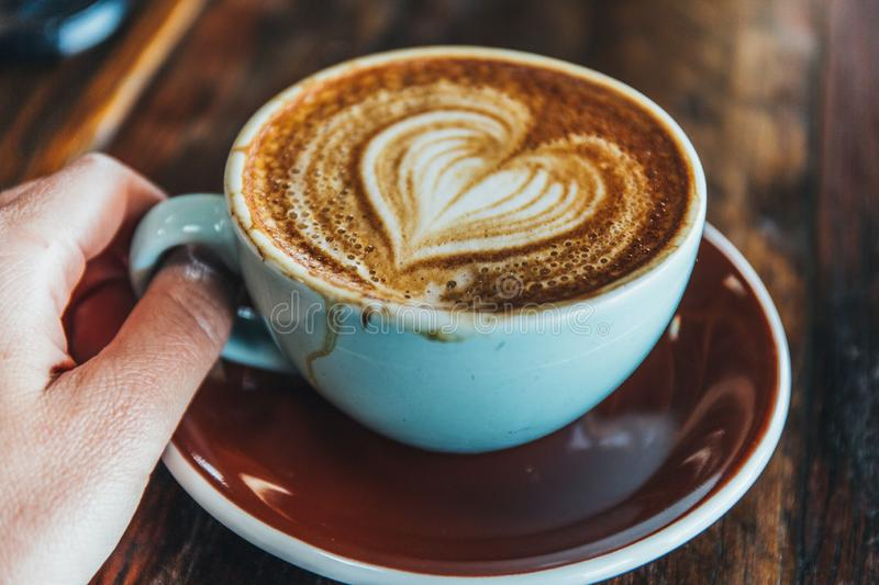 Holding A cup of coffee on wood table stock photography
