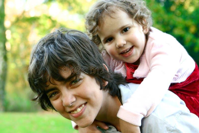 Holding del fratello vicino alla sua più giovane sorella due, immagine stock