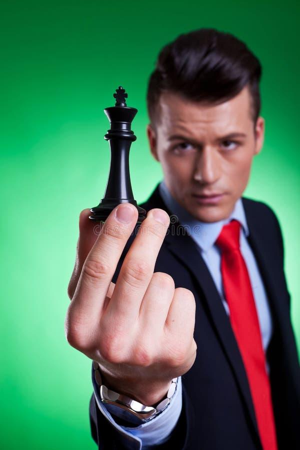 Holding dell'uomo di affari ed esaminare il re nero fotografie stock