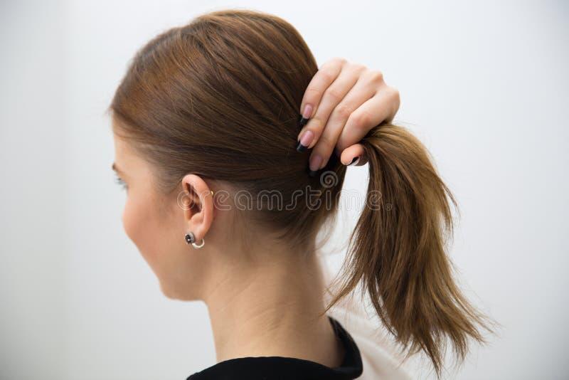 Holding della donna i suoi capelli immagini stock
