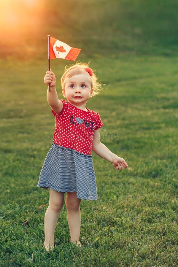 Holding die van het de peutermeisje van de blonde de Kaukasische baby Canadese vlag golven stock fotografie