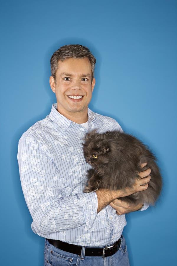 Holding diritta dell'uomo un gatto fotografia stock libera da diritti