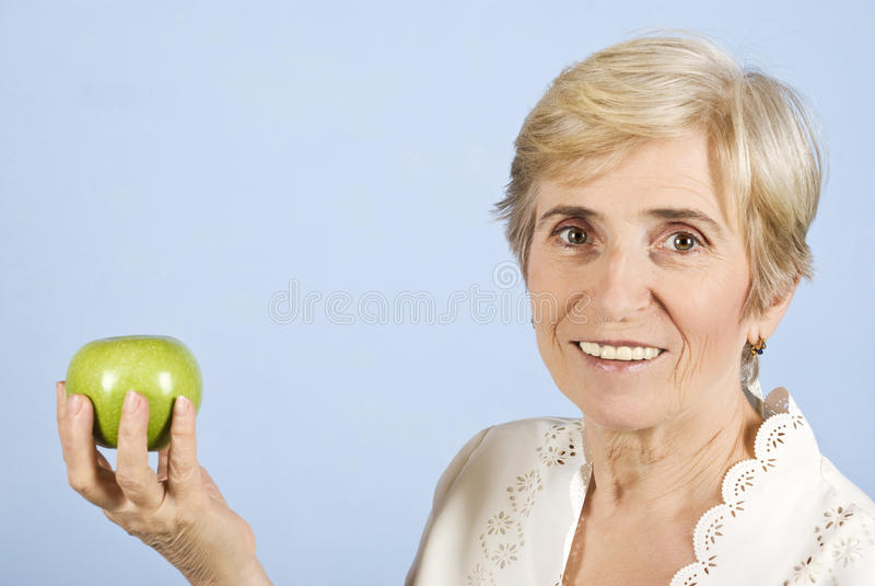 Holding e mela maggiori della donna fotografia stock