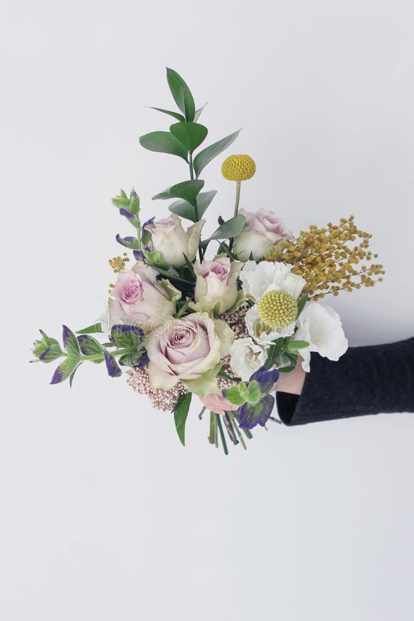 Holding flower bouquet in hand. Woman holding fresh flower bouquet in hand stock photo