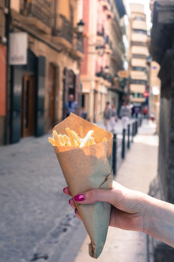 Holding french fries in hand in the street royalty free stock photo