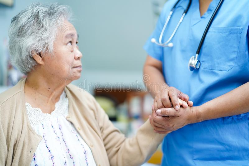 Holding hand Asian senior or elderly old lady patient with love, care, encourage and empathy. Holding hands Asian senior or elderly old lady woman patient with stock photos