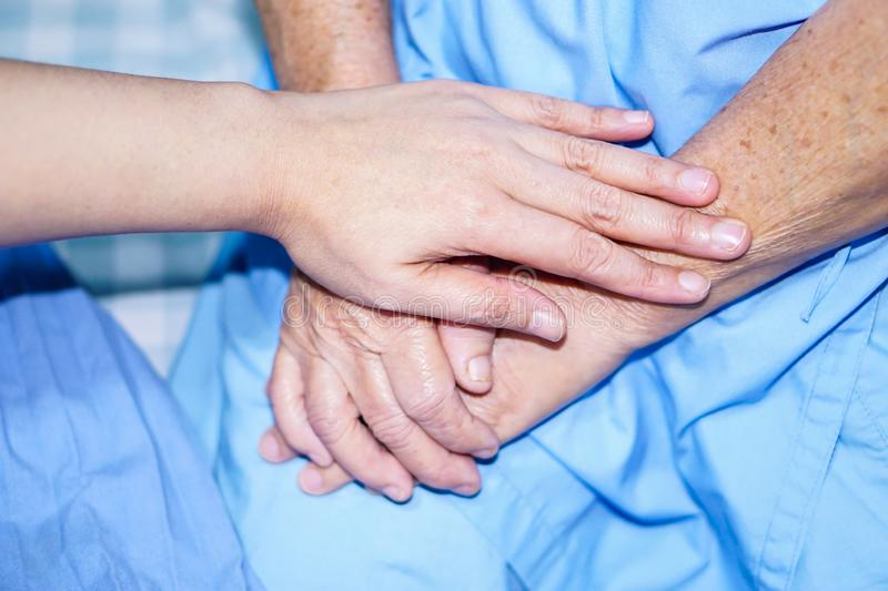 Holding hand Asian senior or elderly old lady patient with love, care, encourage and empathy. Holding hands Asian senior or elderly old lady woman patient with royalty free stock image