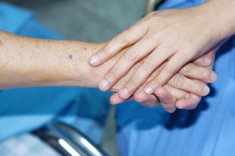 Holding hand Asian senior or elderly old lady patient with love, care, encourage and empathy. Holding hands Asian senior or elderly old lady woman patient with stock image