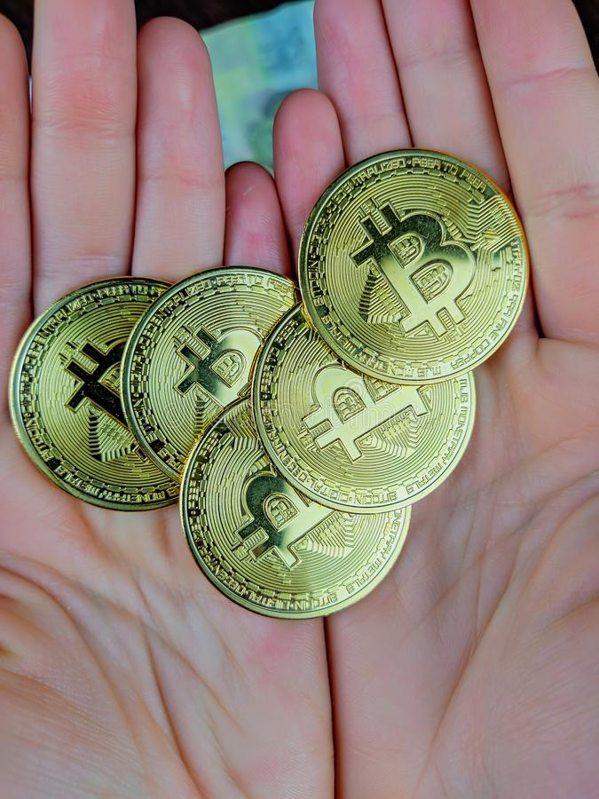 Holding handful of golden bitcoins as a modern cryptocurrency based on blockchain technology and a modern curency for global trade. And investment royalty free stock photo