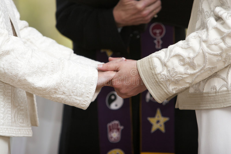 Holding hands. Two women holding hands during a wedding celebration royalty free stock photography