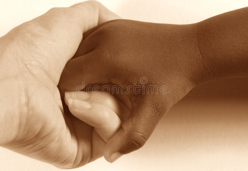 Holding Hands. Diversity. Caucasian adult holding the hand of an African American child