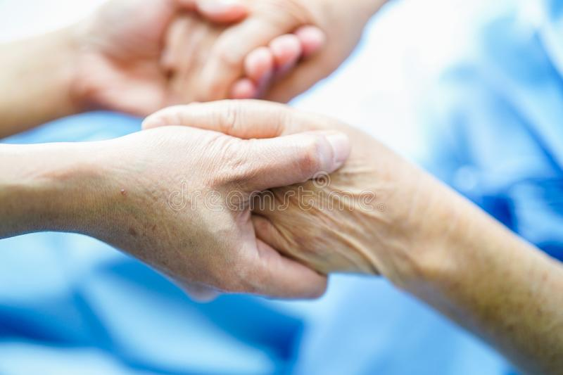 Holding hands Asian senior or elderly old lady woman patient with love, care, encourage and empathy at nursing hospital ward. Healthy strong medical concept stock image