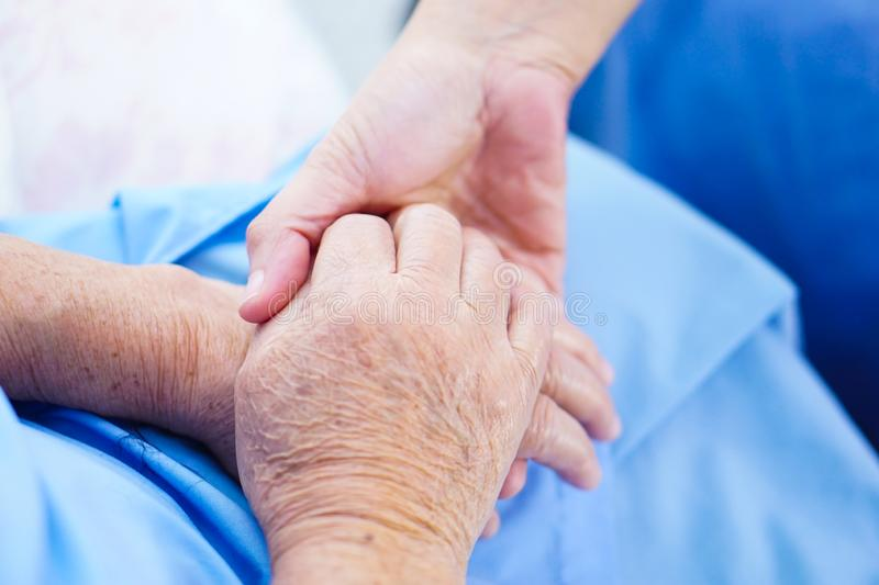 Holding hands Asian senior or elderly old lady woman patient with love, care, encourage and empathy at nursing hospital ward. stock photos