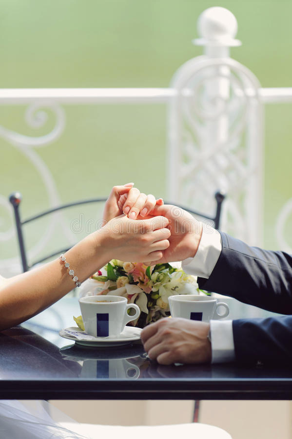 Holding Hands. Bride and groom holding hands in cafe royalty free stock photo