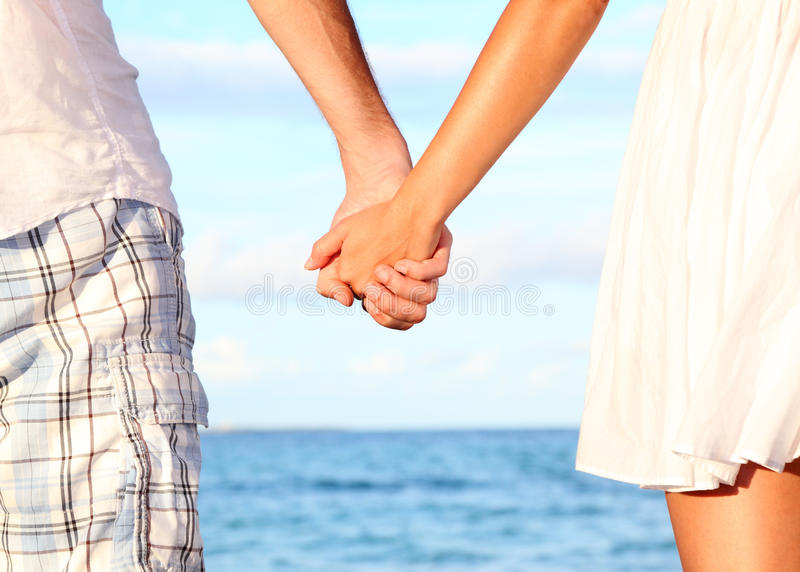 Holding hands couple. On beach. Romantic love and happiness concept image with happy young couple. Closeup
