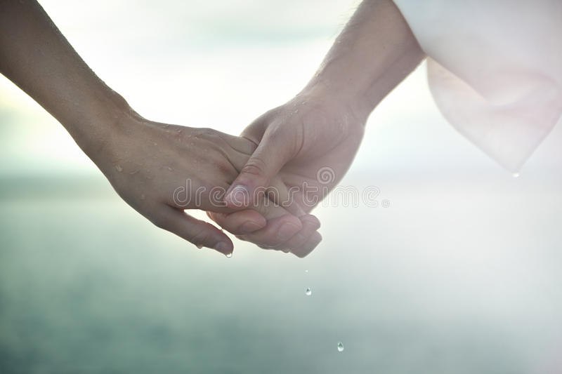 Holding hands. A couple holding hands, waterdrops are falling royalty free stock images
