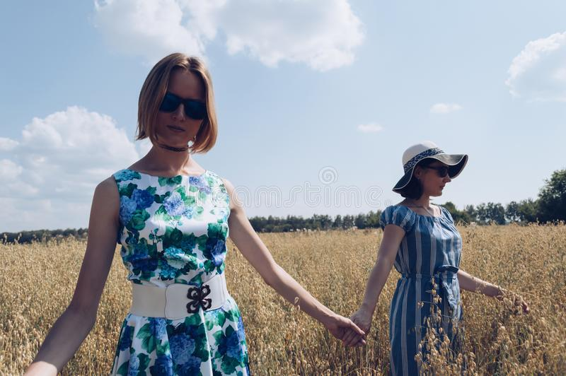 Holding hands female friends in oat field stock photography
