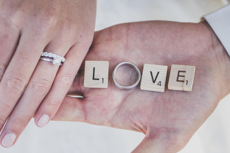 Holding Hands in love. Bride and groom holding love in their hands royalty free stock photos