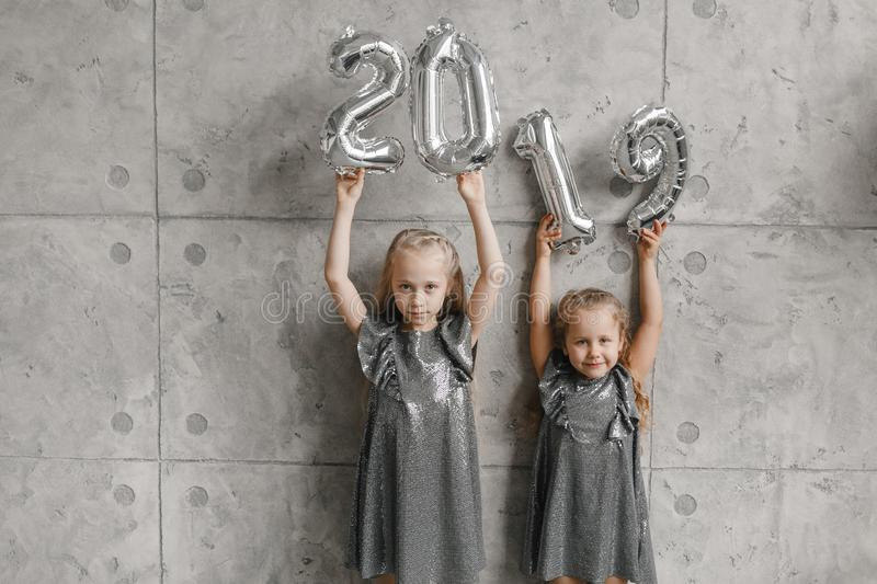 Holding Hands New Year`s Balloons,. Number 2019. Two smile little girls against grey wall background. Christmas time stock images