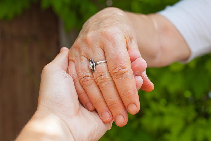 Holding hands, Parkinson disease. Close up young caregiver holding elderly female`s trembling hands, Parkinson disease stock photos