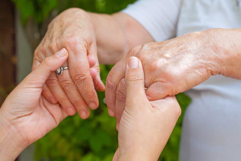 Holding hands, Parkinson disease. Close up young caregiver holding elderly female`s trembling hands, Parkinson disease royalty free stock photo