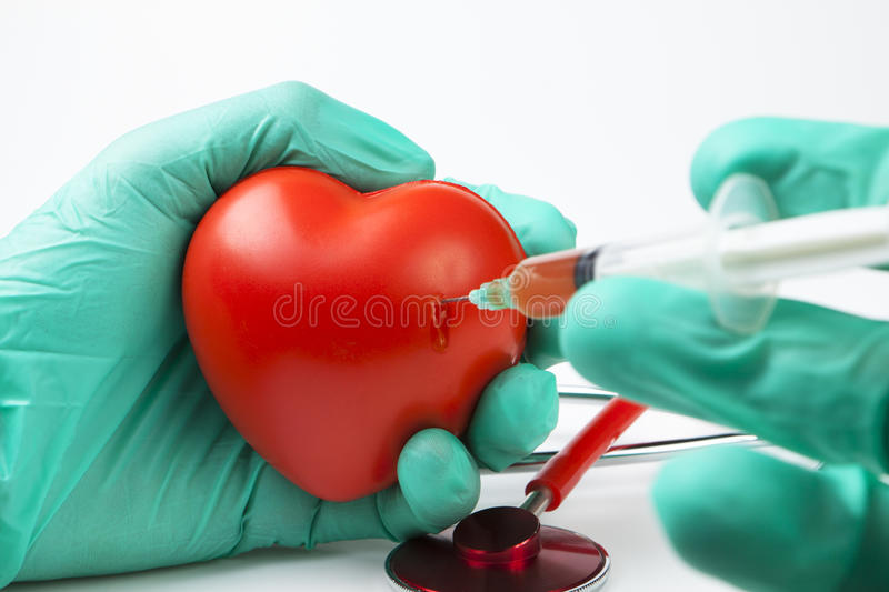 Holding heart. Blood drop while injecting red heart with syringe with two hands green gloves royalty free stock photography