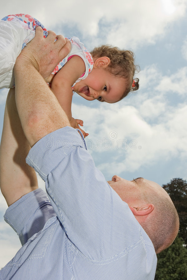Holding her high. Older father holding his little girl high in the sky royalty free stock images