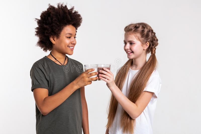 Cheerful appealing kids clinking glasses filled with sweet drinks royalty free stock photos