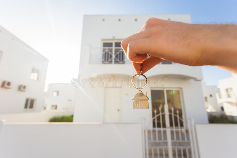 Holding house keys on house shaped keychain closeup in front of a new home. Concept of real estate. Holding house keys on house shaped keychain close up in front stock photo