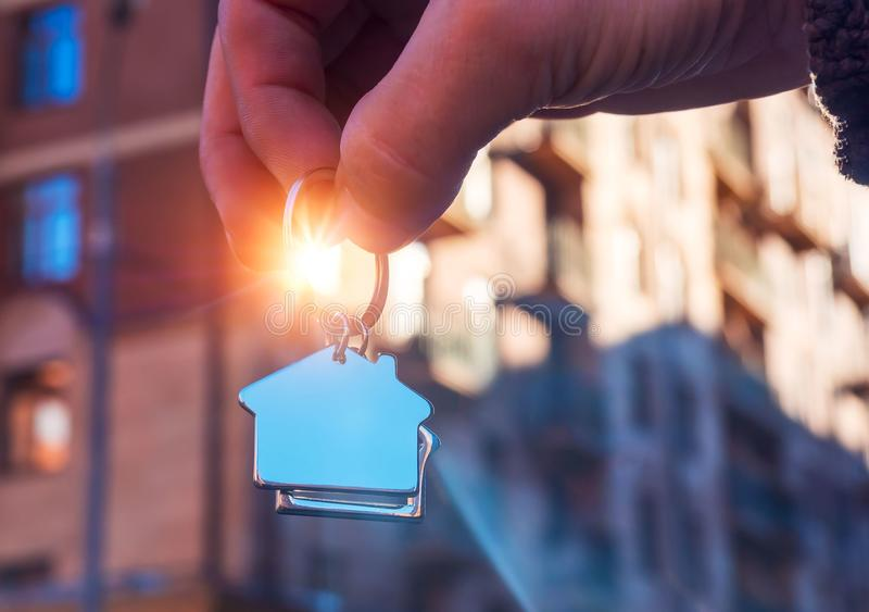 Holding house keys on house shaped keychain. Human hand silhouette holding key to a house isolated on white stock photography