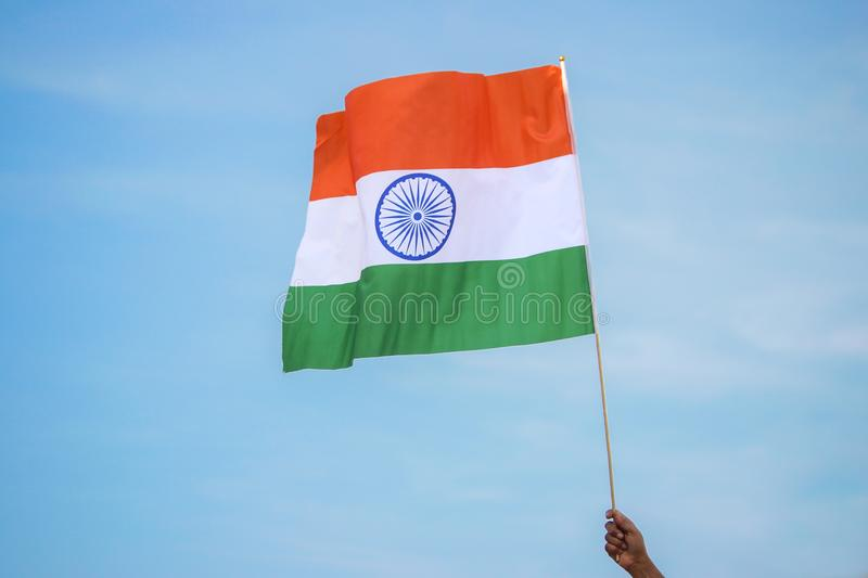 Holding indian tricolor flag on blue sky stock images