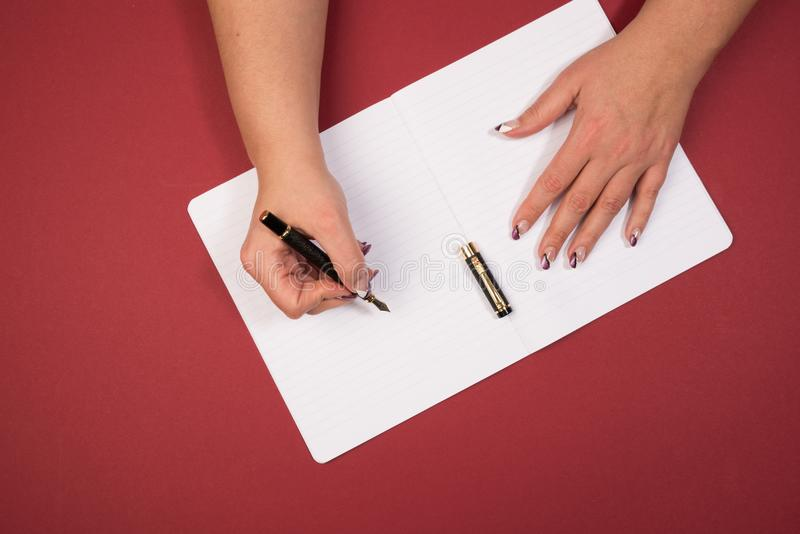 Holding a ink pen in open hand. Holding a ink pen over a notebook on a red desktop stock photography