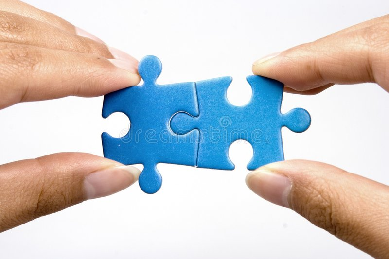 Holding Jigsaw Puzzle. Hands holding two jigsaw puzlle for joining