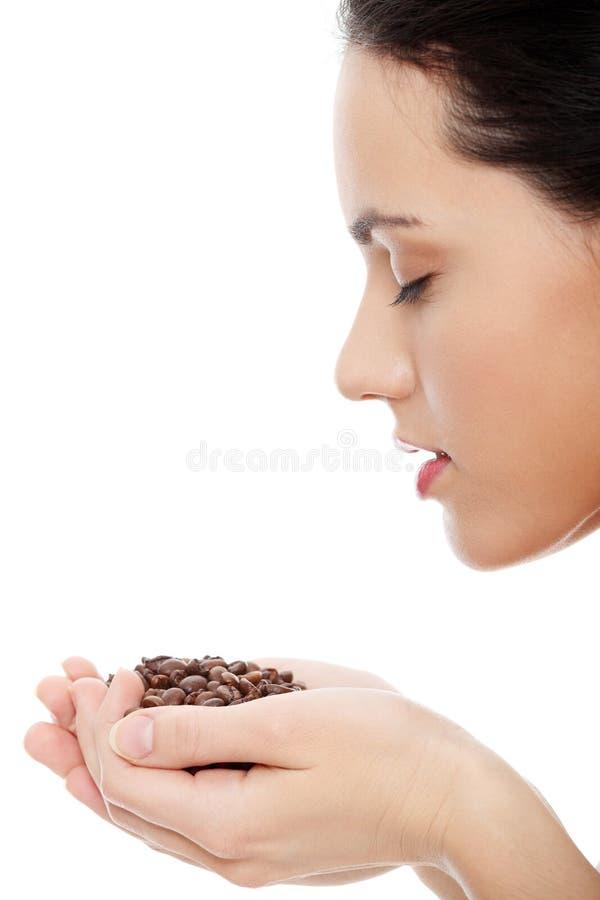 Holding-Kaffeebohnen der jungen Frau stockfotografie